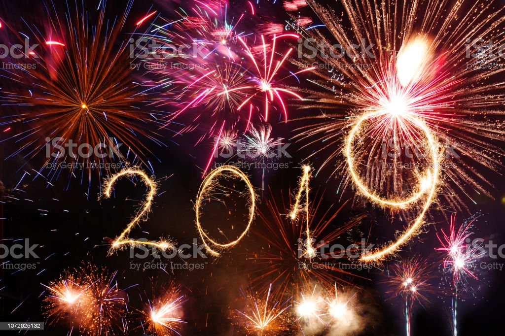 2019 Happy New Year written with Sparkle firework on party background stock photo