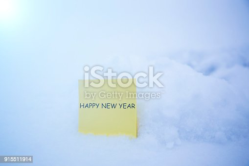 istock happy new year:paper on the snow background 915511914