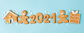 istock Happy New Year's set of numbers 2021, gingerbread man in face mask from ginger biscuits glazed sugar icing decoration on blue background, minimal seasonal pandemic winter holiday banner 1280262589