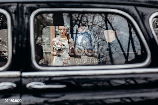 Happy newlywed bride and groom walking towards black car, romantic couple going to limousine outdoors