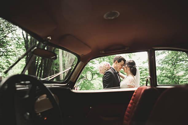 Happy newlywed couple, man and wife kissing near stylish retro stock photo