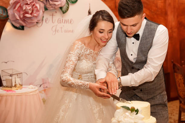 """Happy newlyweds, bride and groom cut wedding cake on the background of the decoration with the inscription """"Je T'Aime"""" stock photo"""