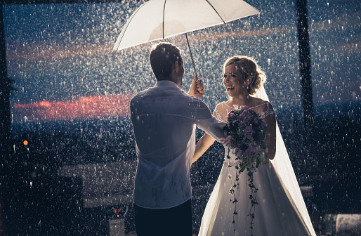 Happily married couple having fun during a rainy day under the umbrella.