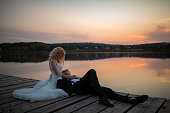Happy newlyweds on pier embracing at sunset