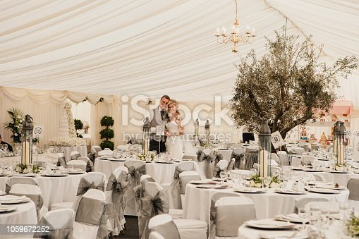 A wide view shot of a happy bride and groom on their wedding day, they are standing next to set tables which are ready for their guests.