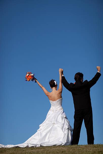 glückliche brautpaar raising hands in celebration, mit textfreiraum - brautkleid trägerlos stock-fotos und bilder