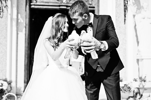 Happy newlyweds with doves at hand background church