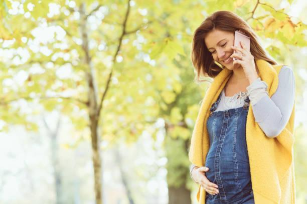 frohe botschaft von der mutter gegeben werden - latzhose für schwangere stock-fotos und bilder