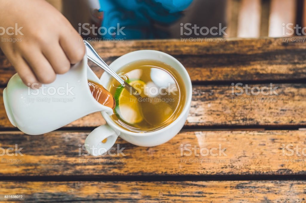 Happy nice boy pours honey into the tea in summer green garden. Portrait. outdoor stock photo