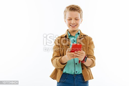 Online chat. Happy nice boy smiling while typing a message on his phone