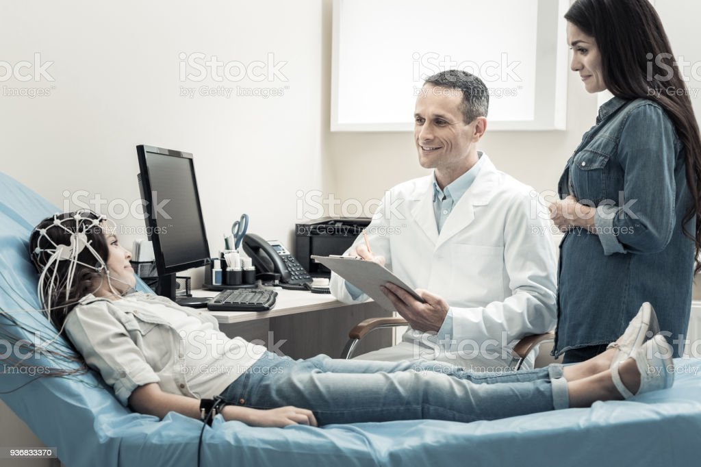 Happy nice doctor looking at his patient stock photo