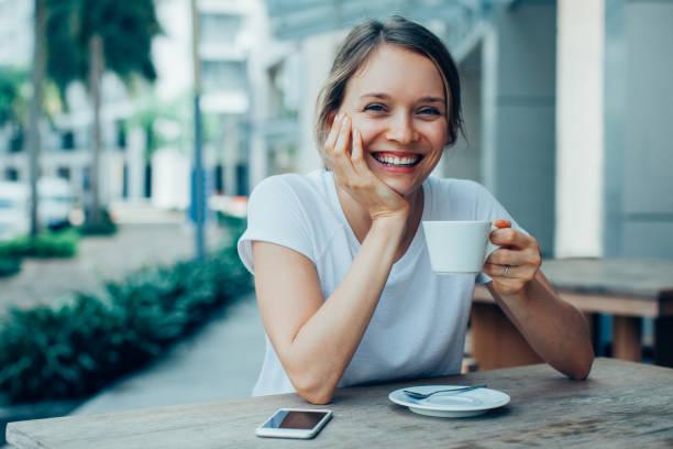 señora bonita feliz tomando café en el café al aire libre - café bebida fotografías e imágenes de stock