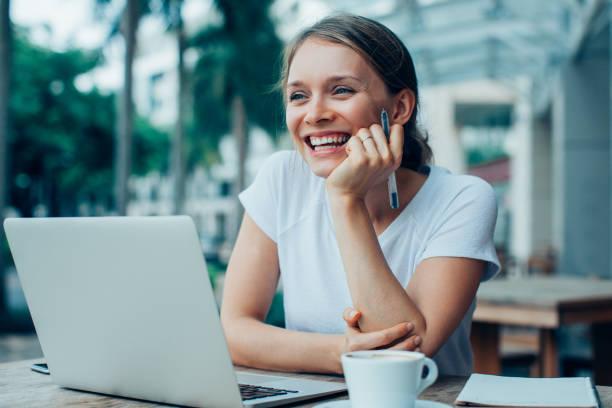 幸福的好女人的街頭咖啡廳在筆記本電腦上工作 - 僅年輕女人 個照片及圖片檔