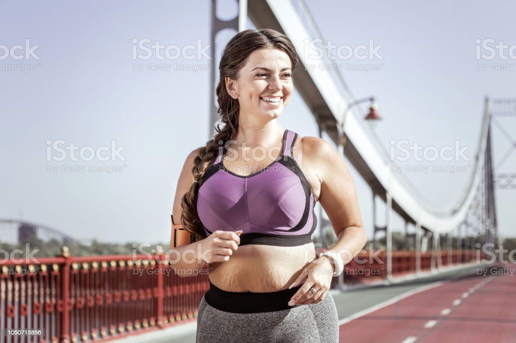 I want to be slim. Happy nice woman running on the bridge while...