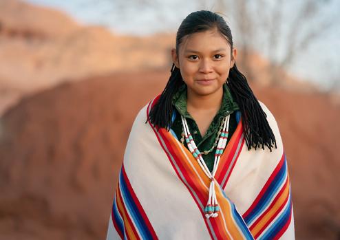 Happy North american indigenous  teen portrait in front of a Navajo hogan