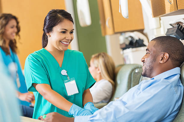 happy nurse comforting patient while he donates blood to hospital - medical research stock photos and pictures