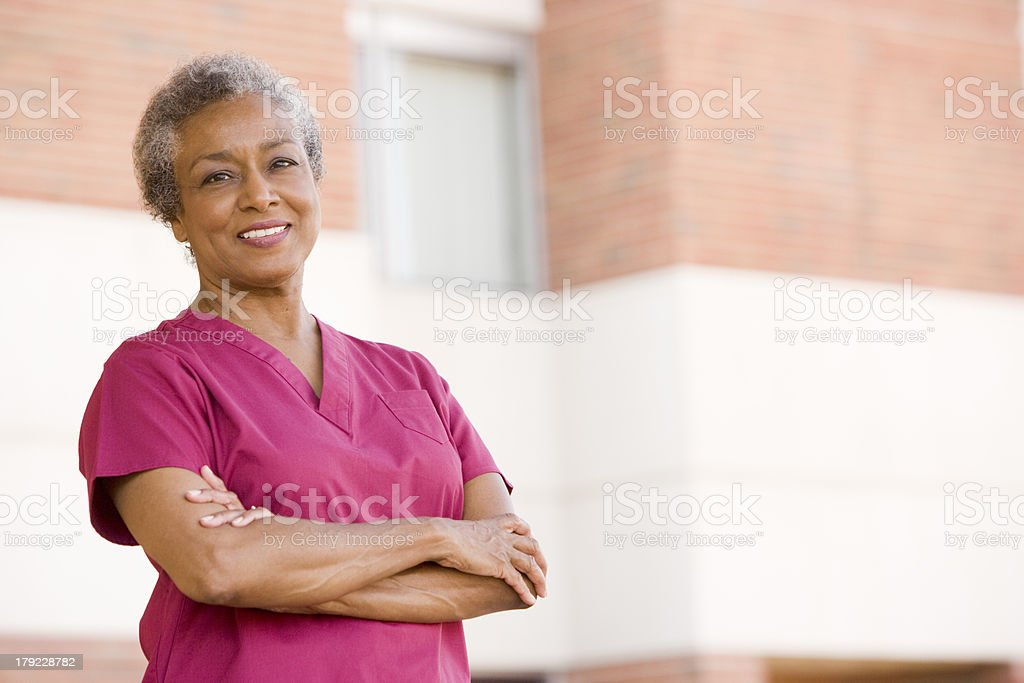 Happy nurse in pink standing outside with arms folded stock photo