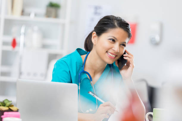 Happy nurse on the phone with a patient Smiling mid adult Asian nurse or doctor is on the phone with a patient. An open laptop is on the desk. filipino ethnicity stock pictures, royalty-free photos & images