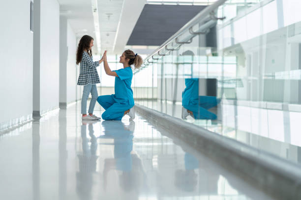 Glückliche Krankenschwester spielt mit einem Mädchen im Krankenhaus – Foto