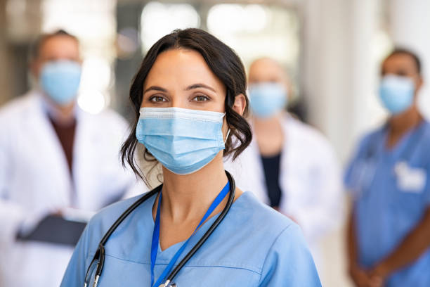 Happy nurse with face mask smiling at hospital stock photo