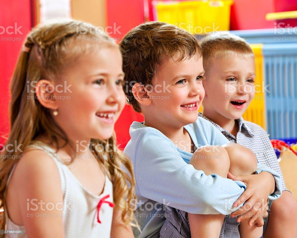 Happy Nursery School Children Cute nursery school children sitting in a playroom and laughing. 4-5 Years Stock Photo