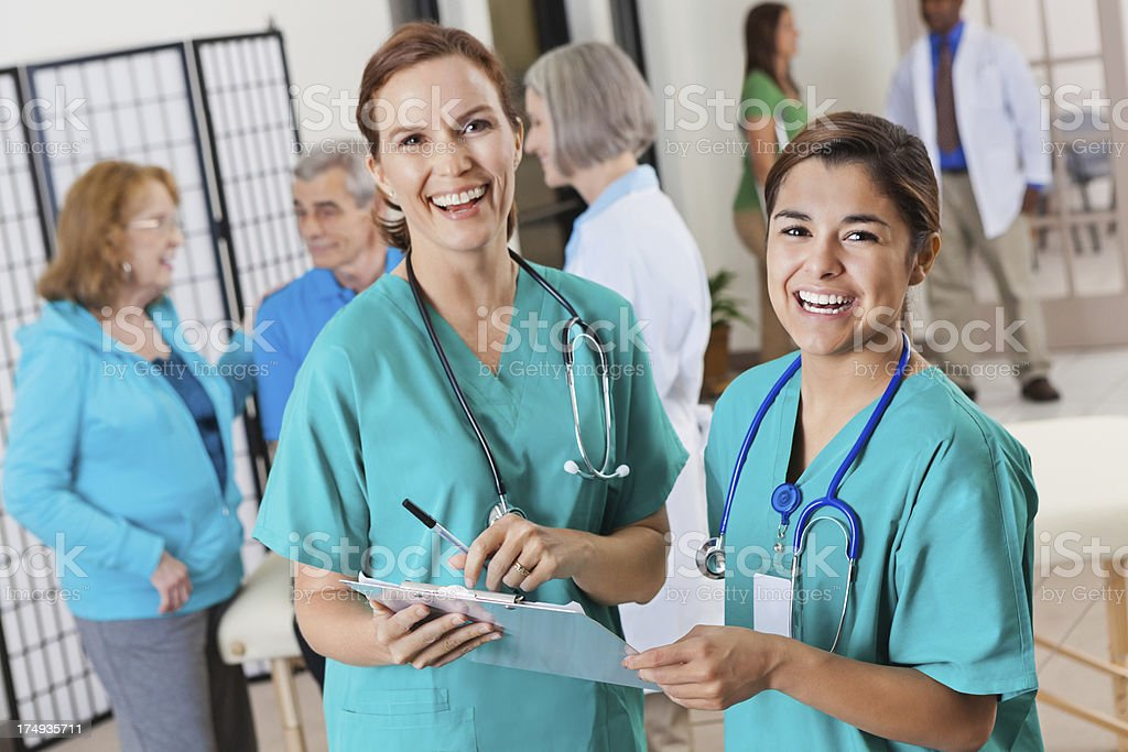 Happy nurses discussing patient chart in busy clinic royalty-free stock photo