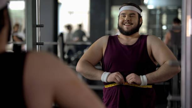 glücklicher übergewichtiger mann messen fette taille zufrieden mit ergebnissen des trainingsprogramms - fett nährstoff stock-fotos und bilder