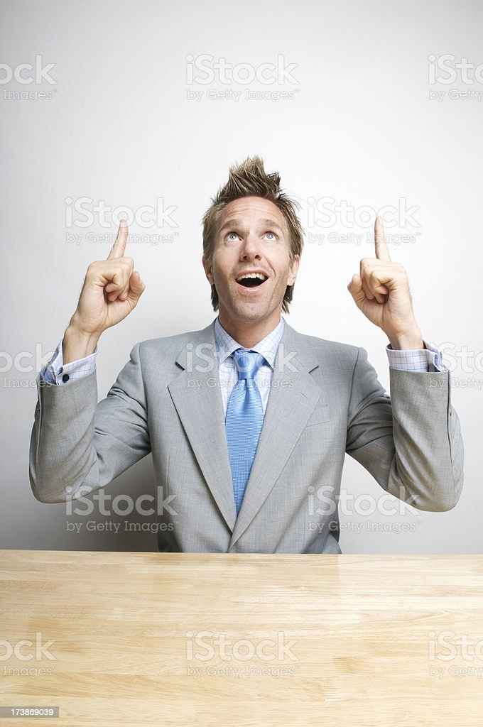Happy Office Worker Businessman Pointing Up Sitting at Desk royalty-free stock photo