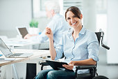 Happy female office worker in wheelchair holding a clipboard and smiling at camera, disabled people support at workplace