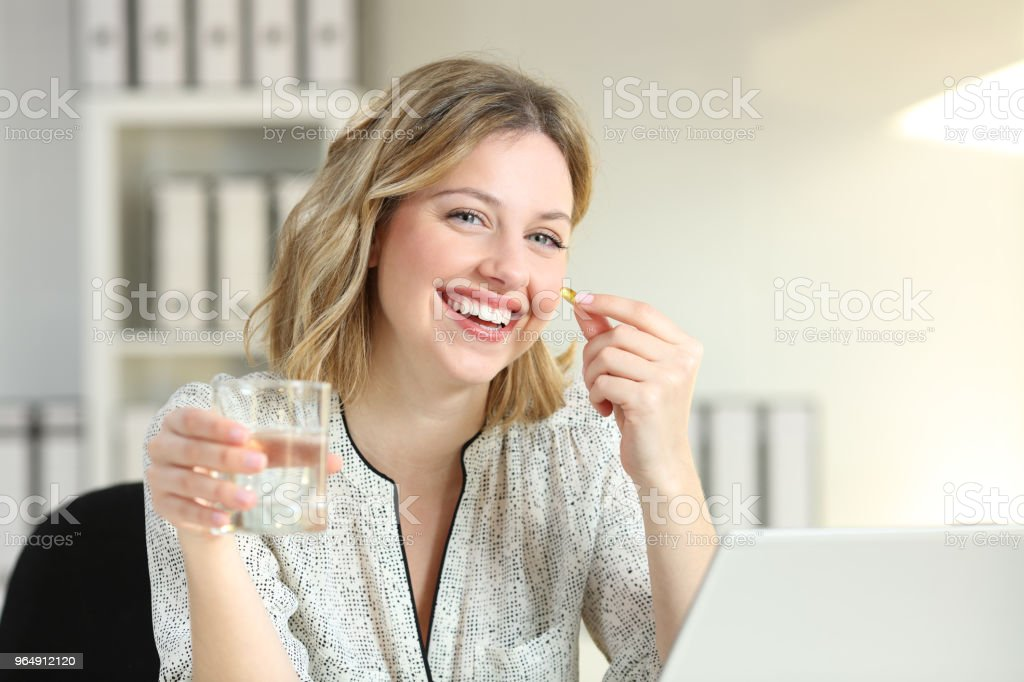 Happy office worker showing a vitamin supplement pill royalty-free stock photo