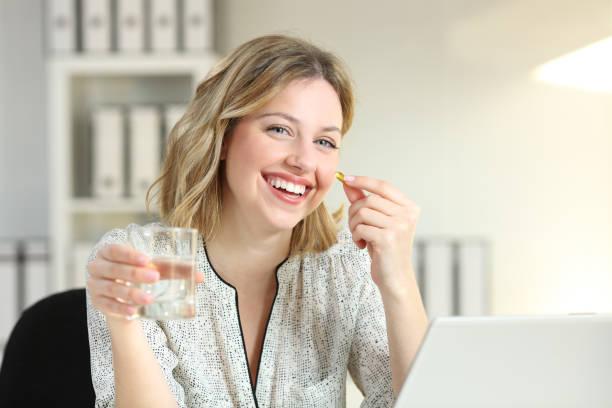 glücklich büroangestellte zeigt eine vitamin ergänzung pille - spanische rezepte stock-fotos und bilder