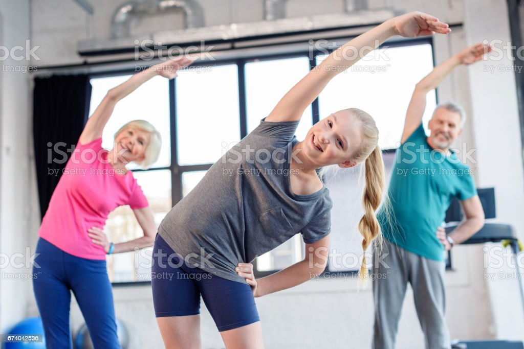 Happy old couple and girl exercising in fitness class for kids and senior people royalty-free stock photo