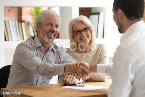 istock Happy old couple clients make financial deal handshake meeting lawyer 1164377564