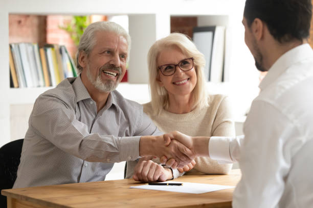 happy old couple clients make financial deal handshake meeting lawyer - family gatherings stock pictures, royalty-free photos & images