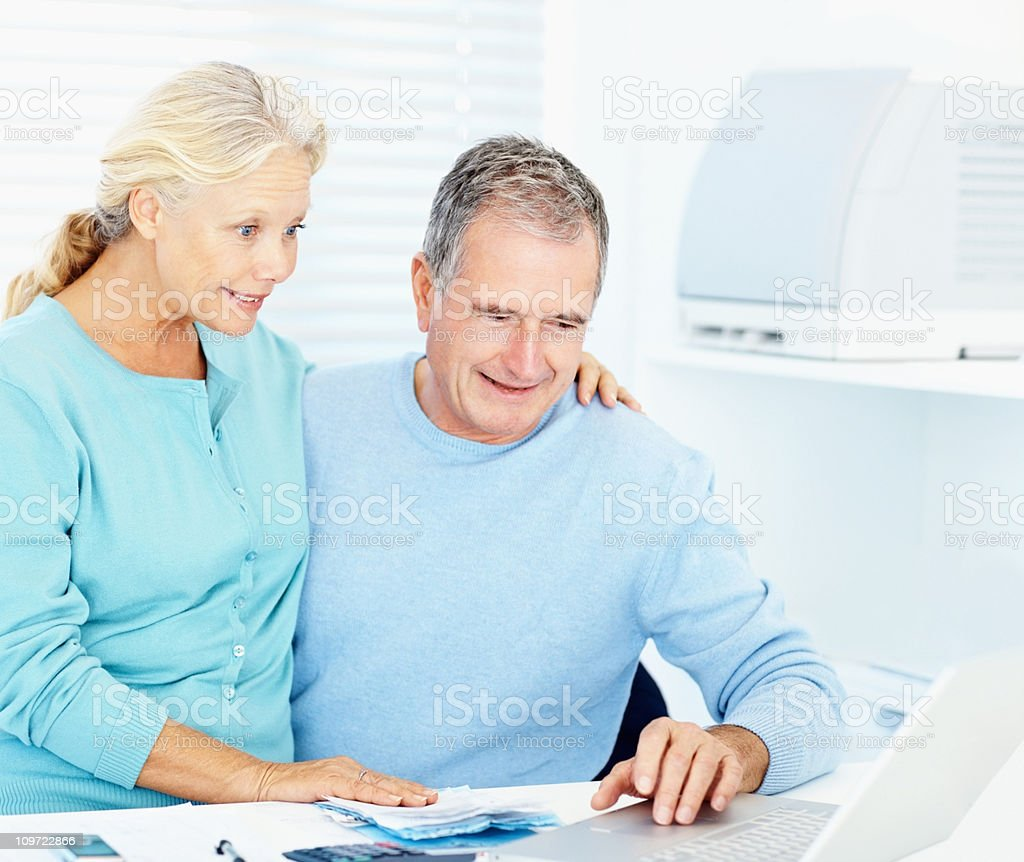 Happy old couple paying bills with online banking at home royalty-free stock photo