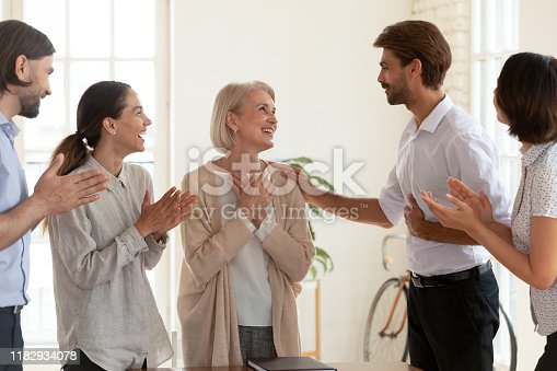 878220300 istock photo Happy old female employee get appreciated by boss and team 1182934078