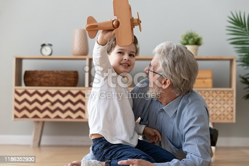 Happy two 2 generation family old grandfather and cute little child boy grandson play hold wooden toy plane lay on floor, funny small grandkid having fun with grandpa fly on airplane laughing at home