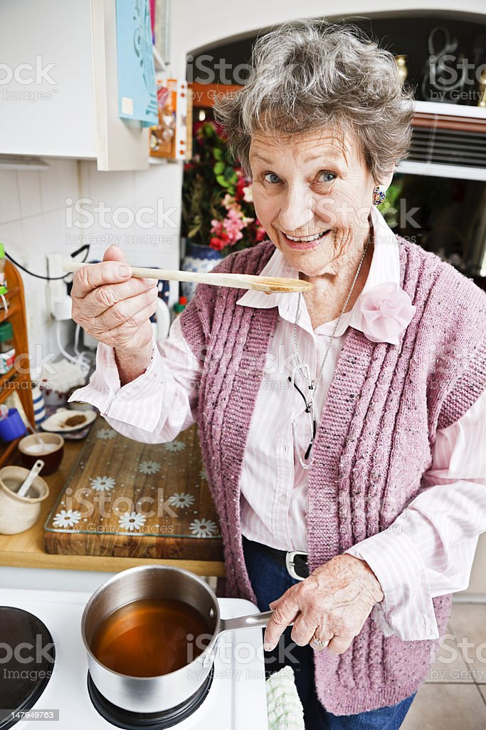 Happy old lady in kitchen smilingly tastes from wooden spoon royalty-free stock photo