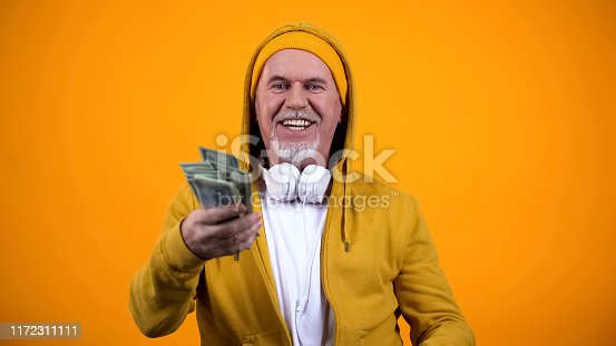 Happy old man in earphones and stylish clothes holding dollars and having fun