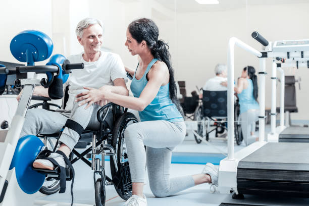 Happy old man in the wheelchair and his smiling trainer Helping others. Happy smiling old grey-haired man sitting in a wheelchair while a content young dark-haired female trainer smiling and standing near him and a training device in front of them drug rehab stock pictures, royalty-free photos & images