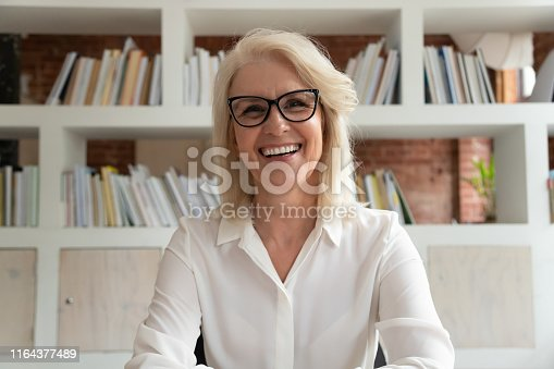 Happy old online teacher tutor look at camera give educational training class lecture teach by webcam, smiling mature business woman talk to webcam make video conference call sit at table in library