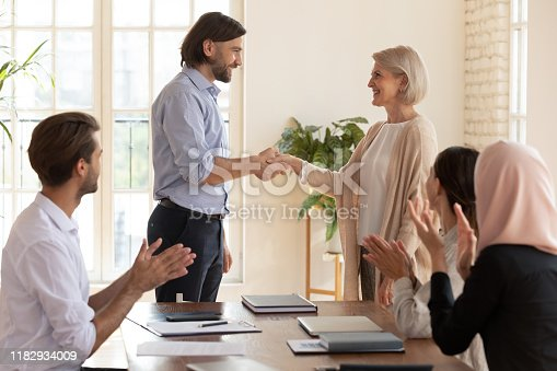 878220300 istock photo Happy old middle aged female employee get promotion team appreciation 1182934009