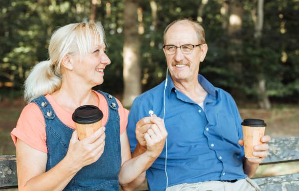 gente feliz compartiendo auriculares. - happy couple sharing a cup of coffee fotografías e imágenes de stock