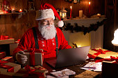 istock Happy old Santa Claus wearing hat holding gift box using laptop computer sitting at workshop home table late on Merry Christmas eve. Ecommerce website xmas time holiday online shopping e commerce sale 1281596611
