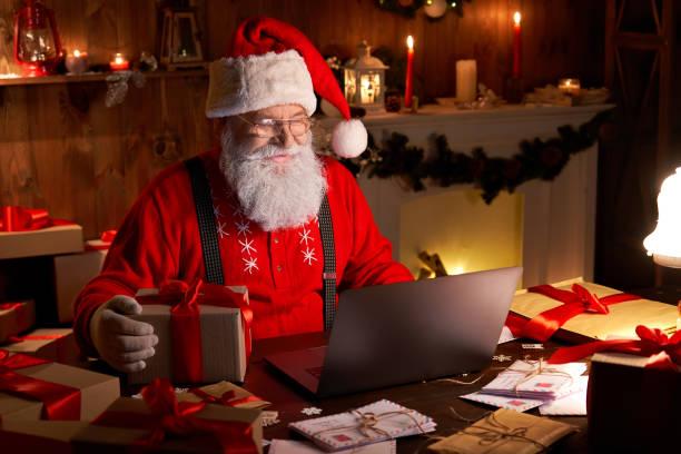 glückliche alte weihnachtsmann trägt hut halten geschenk-box mit laptop-computer sitzt am werkstatt-heimtisch spät am frohen weihnachtsabend. e-commerce-website xmas zeit urlaub online-shopping e-commerce-verkauf - santa stock-fotos und bilder