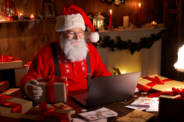glückliche alte weihnachtsmann trägt hut halten geschenk-box mit laptop-computer sitzt am werkstatt-heimtisch spät am frohen weihnachtsabend. e-commerce-website xmas zeit urlaub online-shopping e-commerce-verkauf - nikolaus stock-fotos und bilder