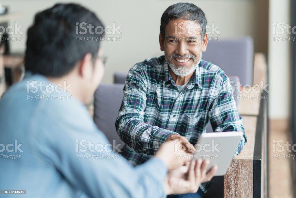 Feliz viejo corto hombre asiático de barba sentado, sonriendo y escucha para asociarse Mostrar presentación en tableta digital inteligente. Hombre maduro con la enseñanza de la tecnología de los medios de comunicación social o concepto de estilo de vi foto de stock libre de derechos