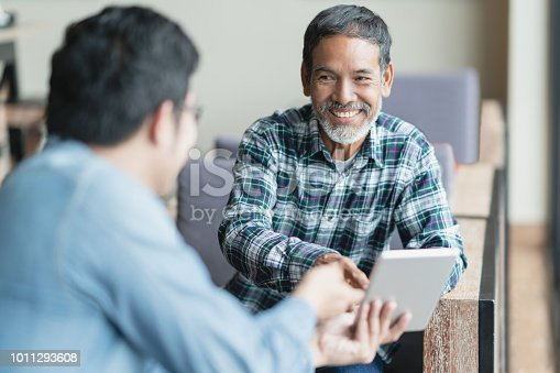 istock Happy old short beard asian man sitting, smiling and listen to partner that showing presentation on smart digital tablet. Mature man with social media technology teaching or urban lifestyle concept. 1011293608