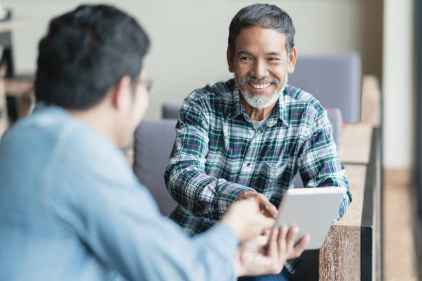 Happy old short beard asian man sitting, smiling and listen to partner that showing presentation on smart digital tablet. Mature man with social media technology teaching or urban lifestyle concept. stock photo