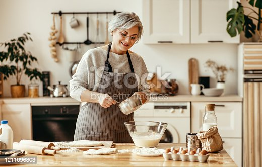 istock happy old woman Granny cooks in kitchen kneads dough, bakes cookies 1211096803